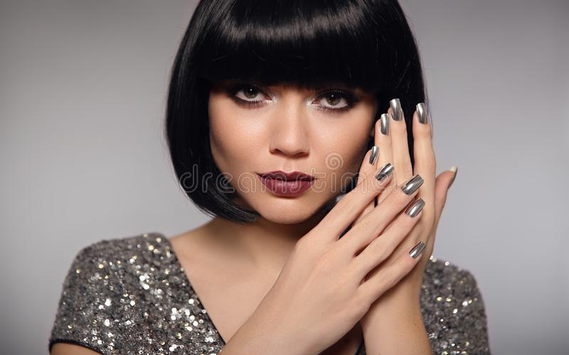 Silver nail art polish manicure. Short bob hair woman model. Fashion brunette close up portrait with beauty makeup and glossy man. Icured nails isolated on gray stock photo