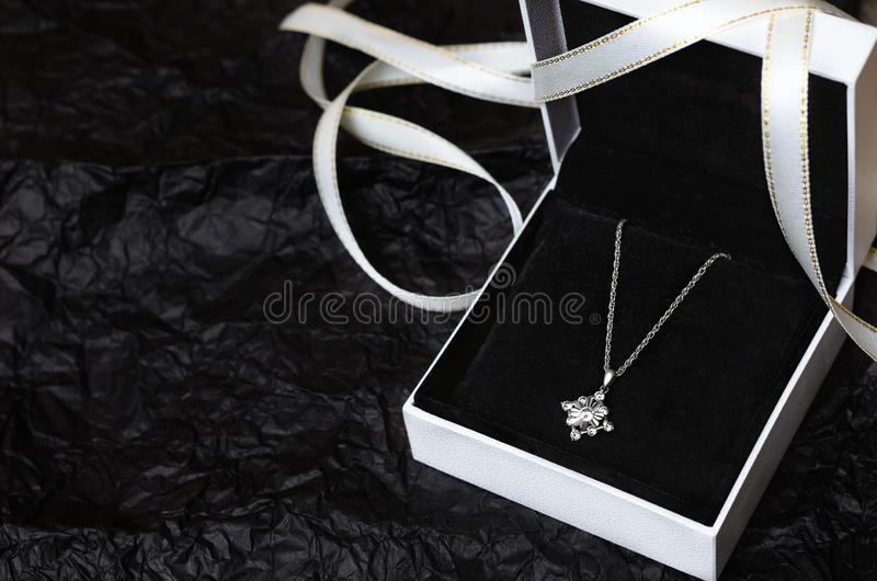 Silver necklace in gift box on black background. royalty free stock image