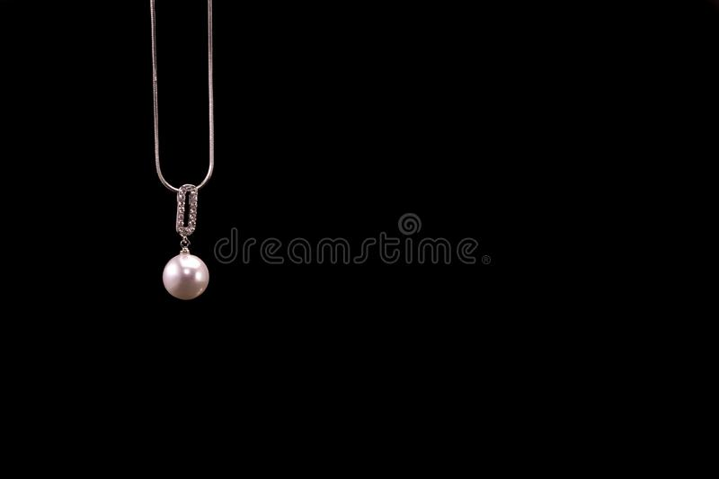 Silver Necklace with Pearl Shaped Pendant isolated on black background royalty free stock photography