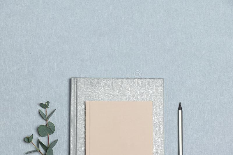 Silver notebook & pencil, pink note, green plant on the grey background stock images