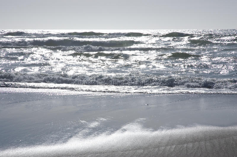 Silver ocean waves. Washing up on beach royalty free stock image