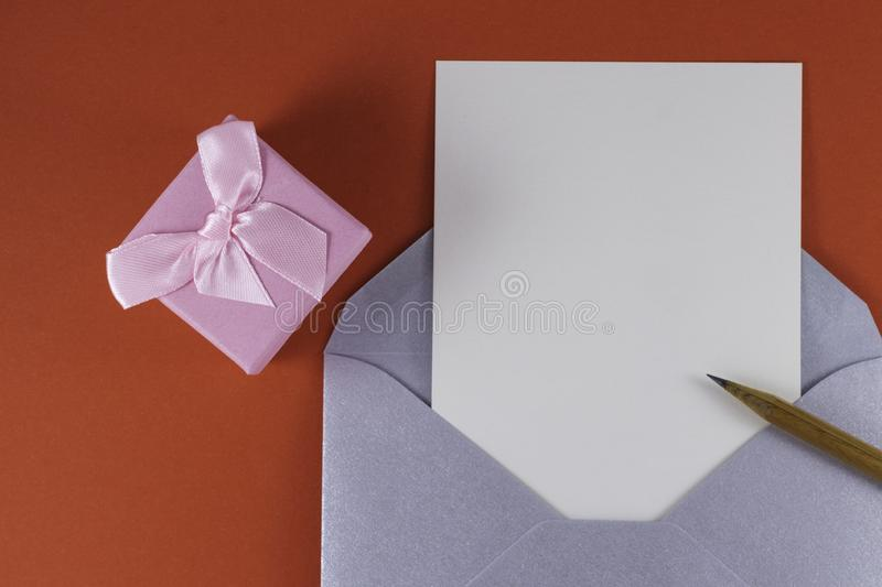 Silver open envelope with white blank letter inside Wooden pencil near and small pink gift box on a red background. Empty Space Letter or invitation Minimalist stock image