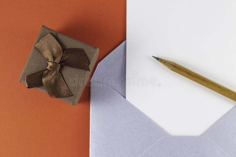 Silver open envelope with white blank letter inside Wooden pencil and small brown gift box on red background. Empty Space Letter or invitation Minimalist stock photo