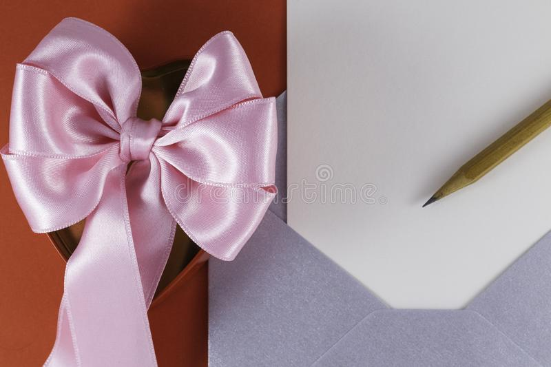 Silver open envelope with white blank letter Wooden pencil Red box with pink big bow. On it Red background Letter or invitation Minimalist concept Copy Space royalty free stock photos