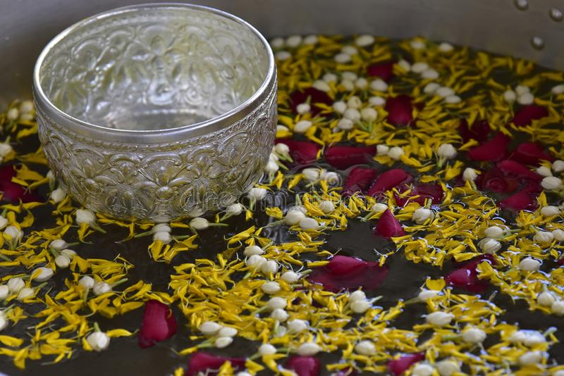 Silver ore bowl floating on the water filled with various kinds of flower petals royalty free stock photos