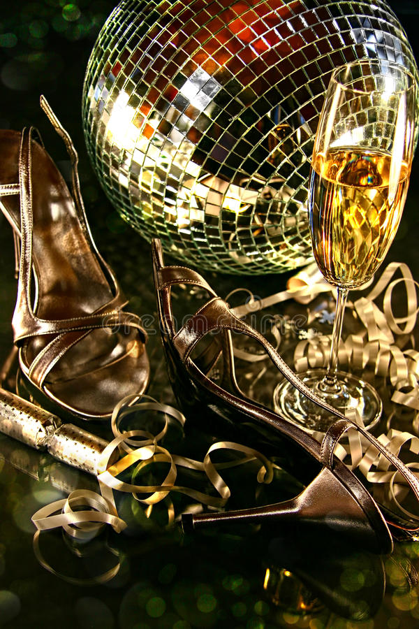 Silver party shoes on floor with champagne glass. For New Year's Eve stock photos