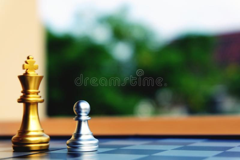 Silver pawn stand at front of Golden king. Little warrior stand up against King royalty free stock photo