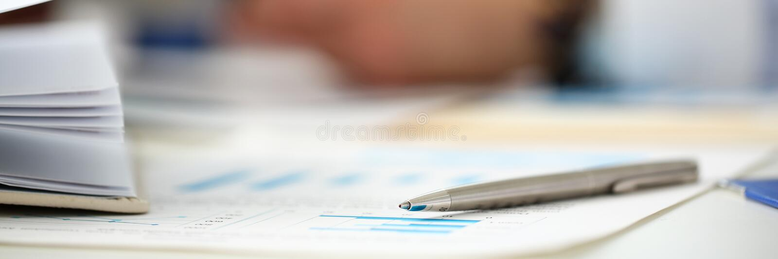 Silver pen lie on important paper at table with group of colleagues in background royalty free stock photo