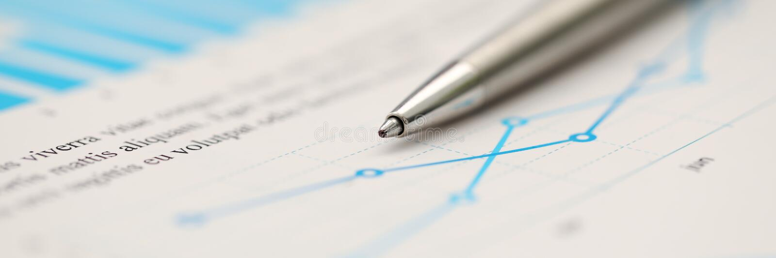 Silver pen lying down at important statistic document at empty working table. Macro royalty free stock image
