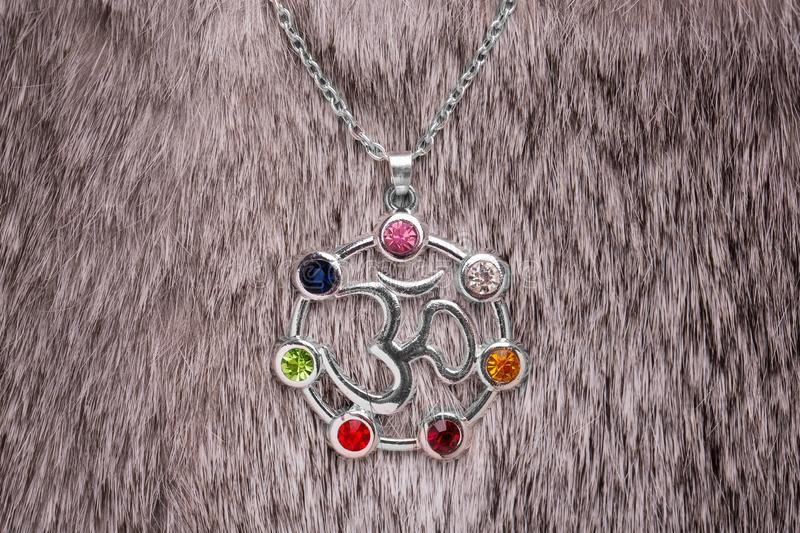 Silver pendant with OM sign. OM sign on a silver pendant surrounded by colored gemstones. OM on gray fur, element, jewelry, background, decoration, accessory stock images