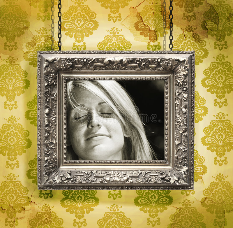 Silver picture frame against floral wallpaper. Silver picture frame hung against floral wallpaper background royalty free stock image
