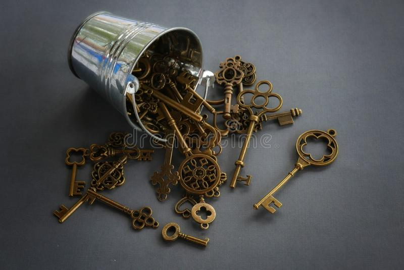 Silver pile and bunch of keys on dark vignette grey background royalty free stock photo