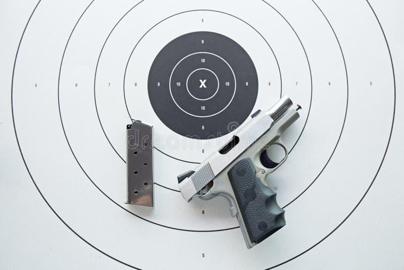 silver pistol 45 med tidskriften på bullseyemål arkivfoton
