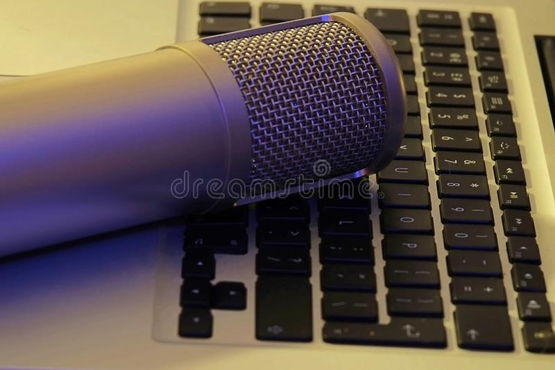 Podcast Microphone on laptop computer keyboard. Silver podcast microphone over laptop computer keyboard Media broadcast live news royalty free stock photos