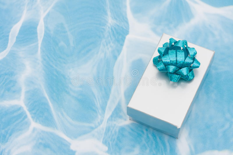 A Silver Present With Bow On Aqua Background Stock Photography