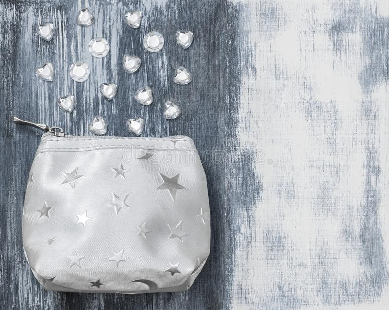 Silver purse and glass beads on artistic background royalty free stock image
