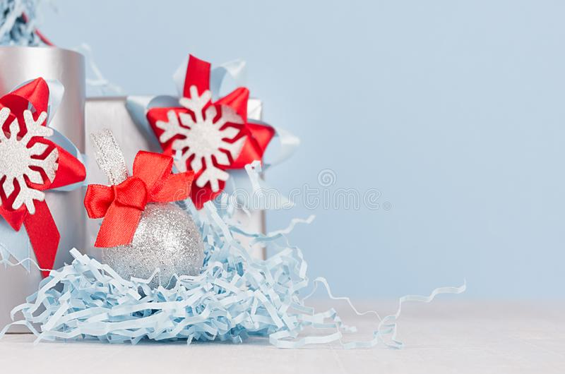 Silver shiny ball with red silk bow closeup and festive christmas decorations and gift boxes on soft light blue color background. royalty free stock images