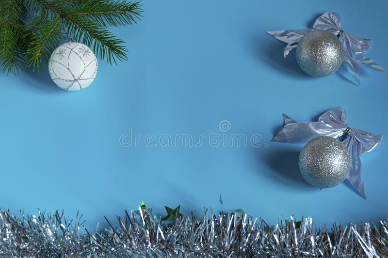 Silver shiny Christmas decorations, spruce branch, balls for the Christmas tree, bows, tinsel on a blue background, top view. Silver shiny Christmas decorations stock photo