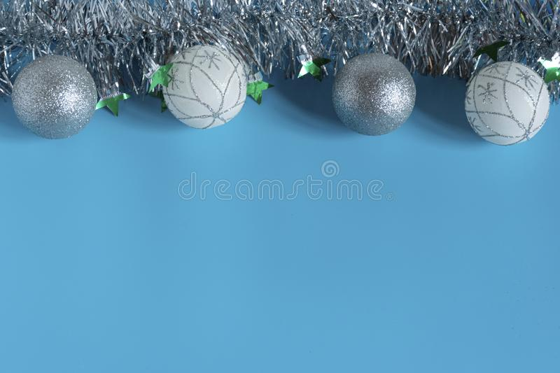 Silver shiny Christmas decorations, spruce branch, balls for the Christmas tree, bows, tinsel on a blue background, top view. Silver shiny Christmas decorations royalty free stock images