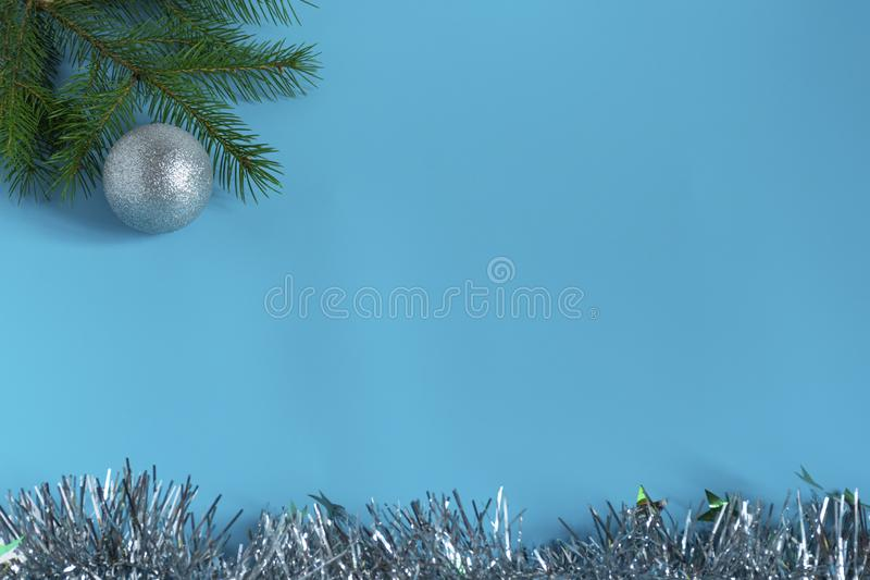 Silver shiny Christmas decorations, spruce branch, balls for the Christmas tree, bows, tinsel on a blue background, top view. Silver shiny Christmas decorations stock images