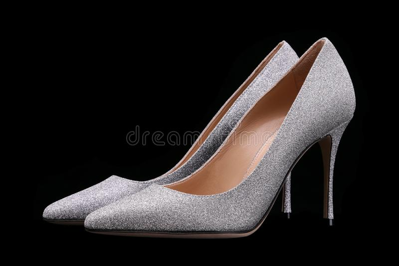 Silver shiny high-heeled shoes with a pointed toe. Women shoes. A pair of beautiful female shoes on a black background, high, heel, silver, shine, elegant stock image