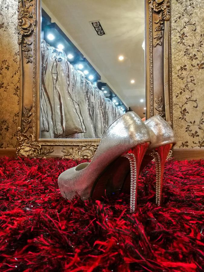 Silver shiny high-heeled shoes stiletto on red carpet in wedding stock image