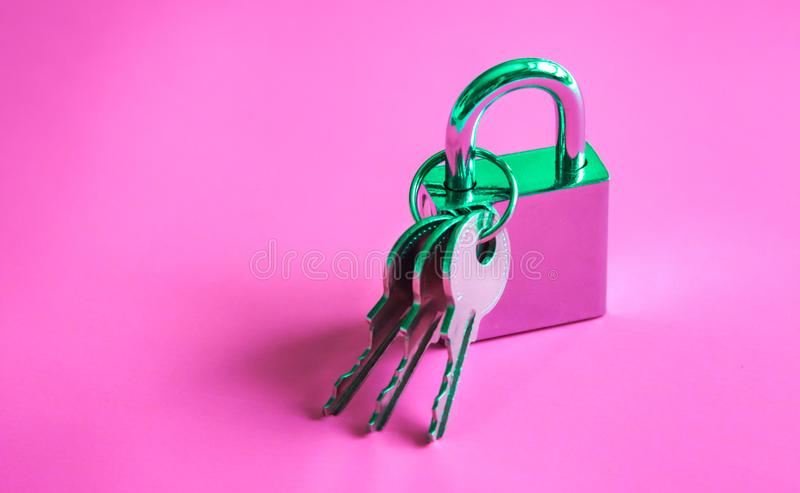 Silver padlock and keys background. Silver shiny padlock and three keys on vibrant lilac pink gradient holographic color. Concept art stock images