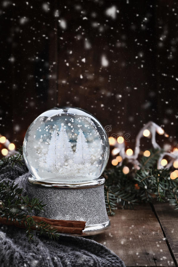 Silver Snow Globe. Rustic image of a snow globe surrounded by pine branches, cinnamon sticks and a warm gray scarf with gently falling snow flakes stock images