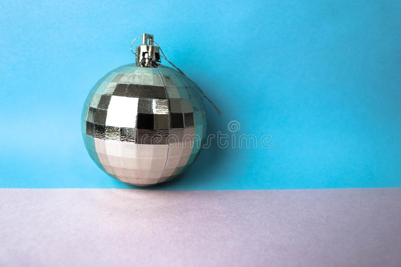 Silver snowy small round xmas festive Christmas ball, Christmas toy plastered over sparkles on a gray blue background royalty free stock images