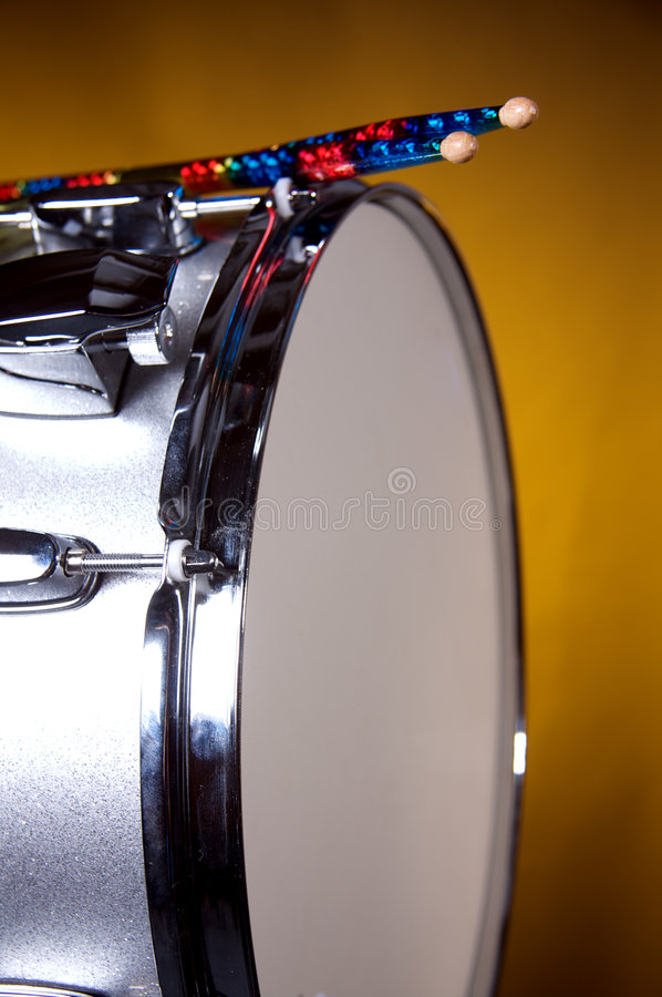 Silver Sparkle Snare Drum on Gold. A silver sparkle snare drum with multicolored drumsticks isolated against a gold or yellow background in the vertical format royalty free stock photos