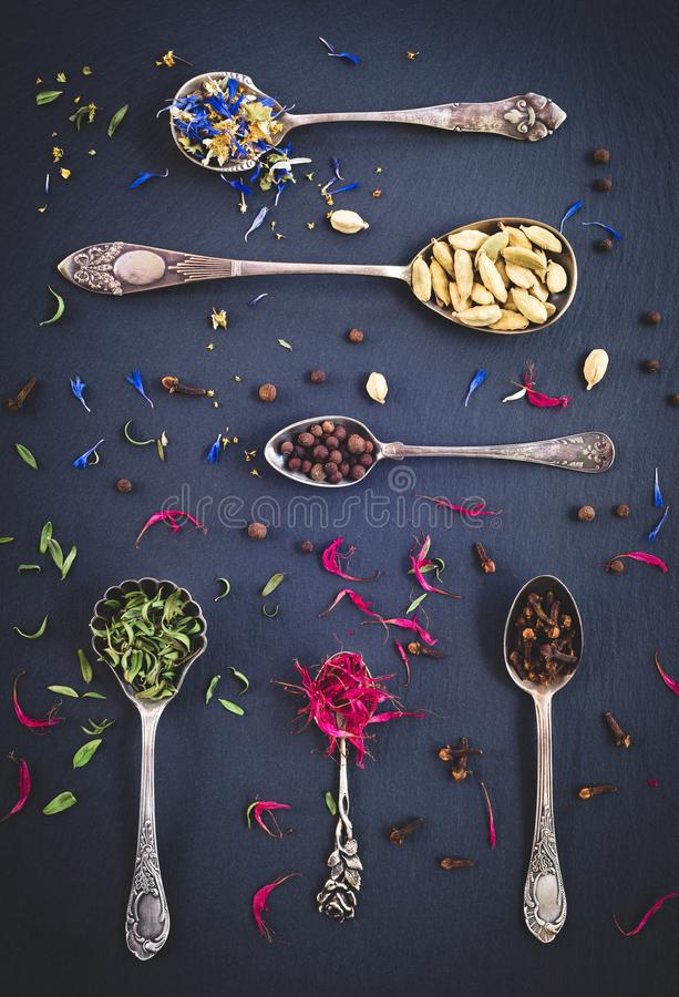 Silver spoons full of spices and herbs royalty free stock photo