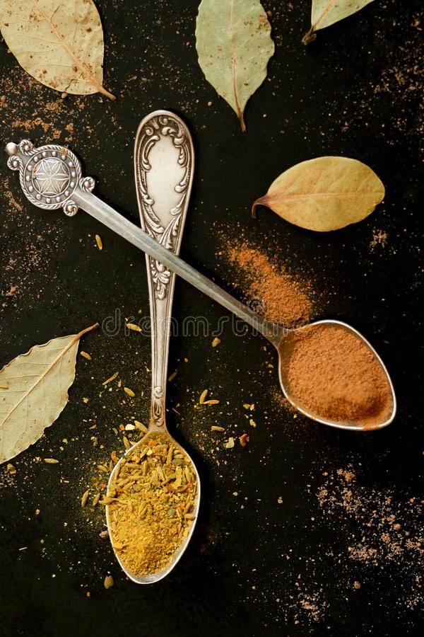 Silver spoons with spices royalty free stock images