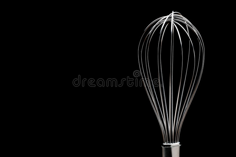 A silver stainless steel whisk. On a black background royalty free stock photo