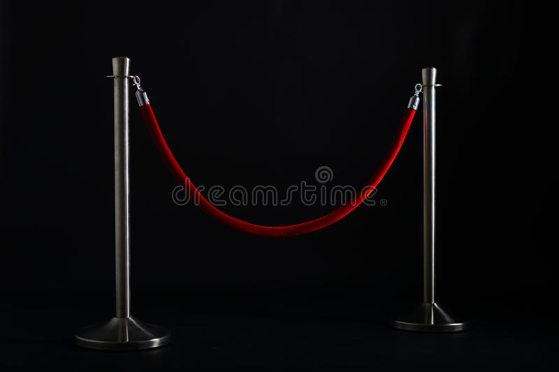 Silver stanchions with a red rope royalty free stock photos