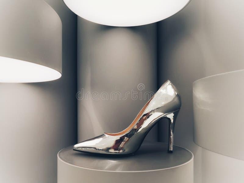 Silver stiletto on display. Shiny silver stiletto on futuristic display royalty free stock photos