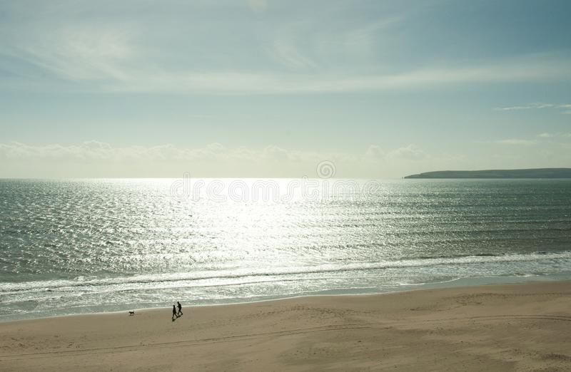 Silver sunset on Preston beach in the summertime. A summertime scene along Preston beach in Dorset, United Kingdom with a surfer riding the silver seas royalty free stock photography