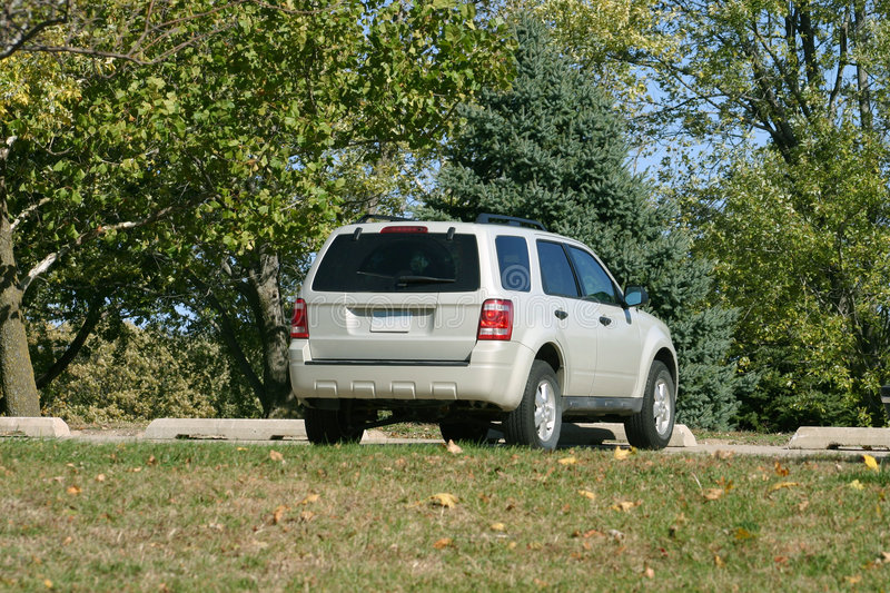 Silver SUV. A new silver SUV parked at a park stock photography
