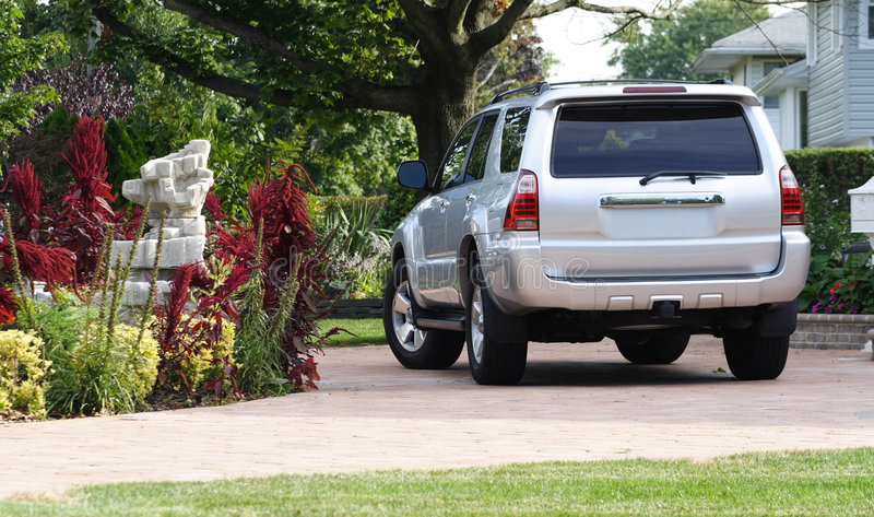 Silver SUV in Driveway. Rear view of silver sport utility vehicle in circular driveway royalty free stock image