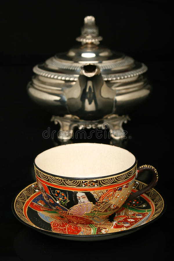 Silver teapot and an antique chinese cup of tea royalty free stock images
