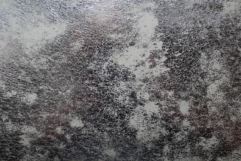 Silver texture with attrition on imitation leather. Silver background of the shining skin design of old metal rust. Gray shabby texture for a decor of works royalty free stock photography