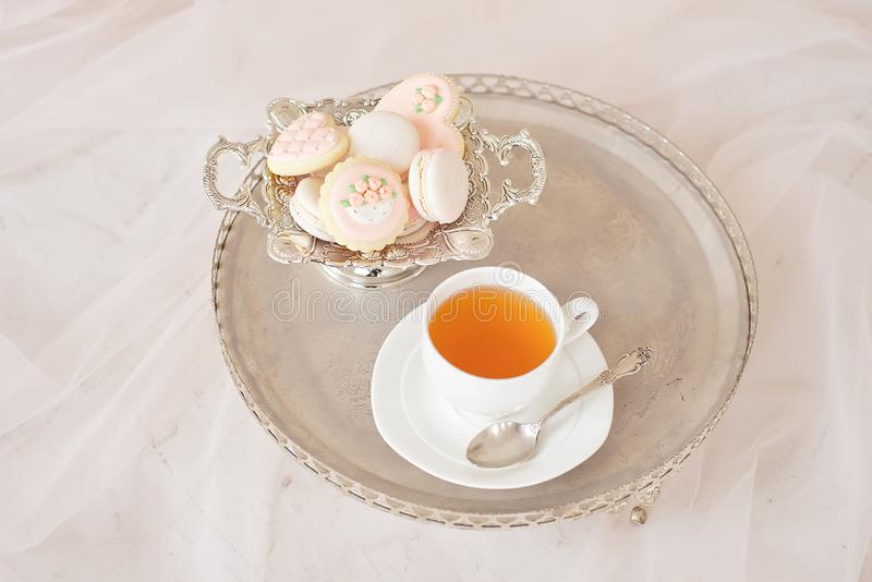 Silver tray with a cup of tea and macarons on a wooden white table in a white room royalty free stock images