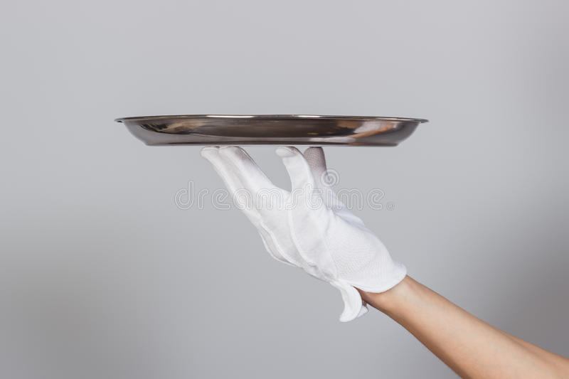 Silver tray in the hand, gray background. Hand in glove with a silver tray on the gray background royalty free stock image