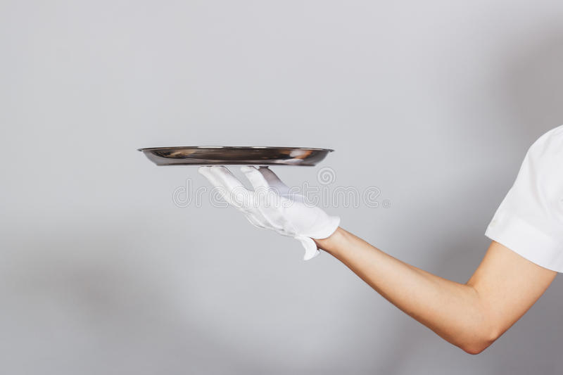 Silver tray in the hand, gray background. Hand in glove with a silver tray on the gray background stock photography