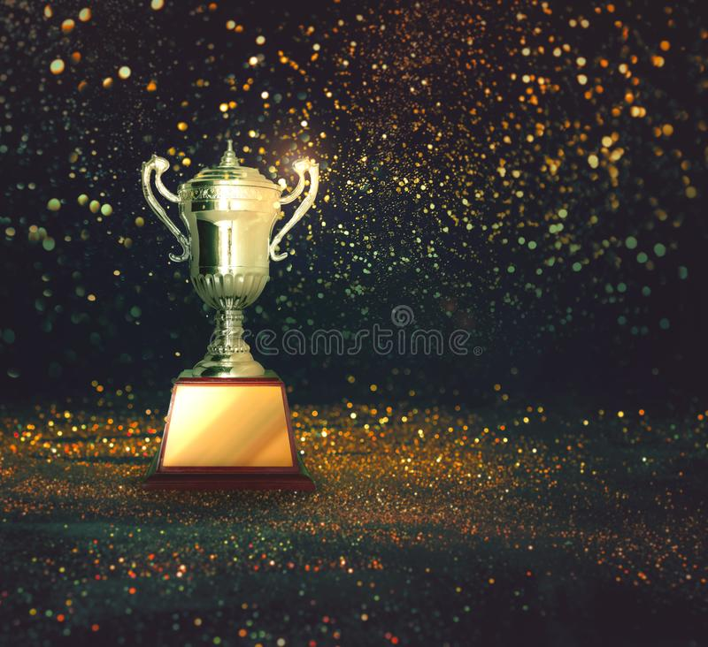 Silver trophy on abstract gold glitter background. stock image