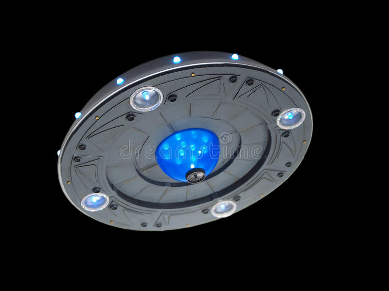 Silver UFO. Underside view of a silver UFO traveling against a black background stock image