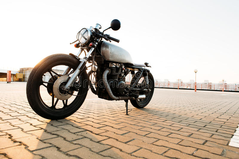 Silver vintage custom motorcycle cafe racer. Brutal custom vintage motorbike cafe racer punk motorcycle with raw metal gas tank and tape cross over optic at royalty free stock images