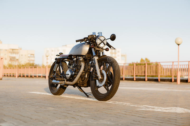 Silver vintage custom motorcycle cafe racer. Front view of silver vintage custom motorcycle cafe racer motorbike on empty rooftop parking lot surrounded by urban stock photography