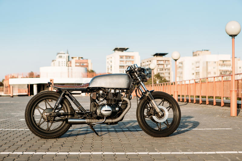 Silver vintage custom motorcycle cafe racer. Silver vintage custom motorcycle motorbike caferacer on empty rooftop parking lot at city center surrounded by urban royalty free stock images