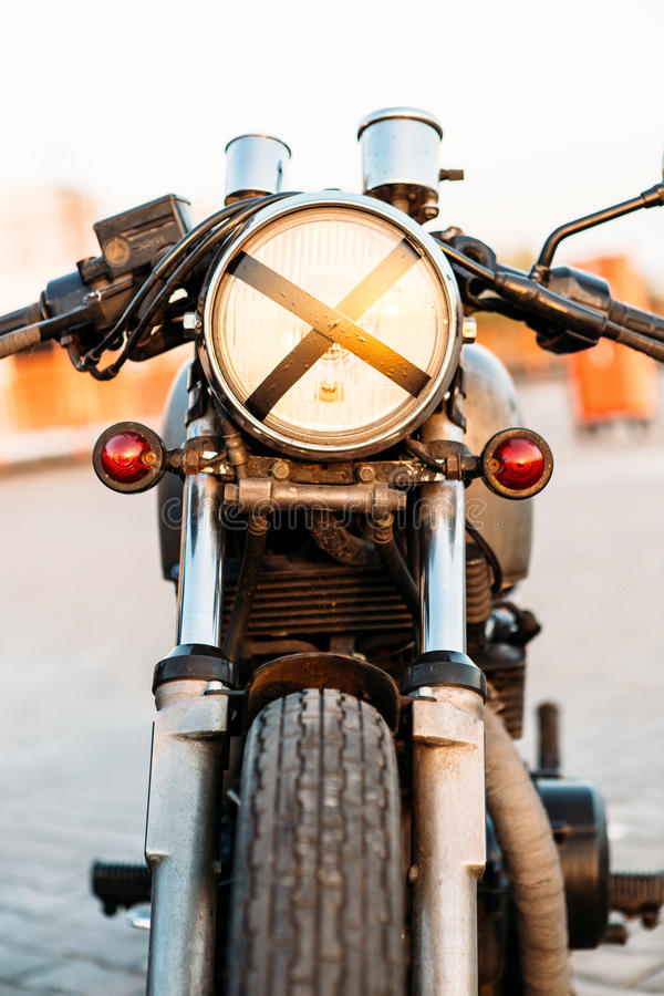 Silver vintage custom motorcycle cafe racer. One vintage custom motorcycle cafe racer motorbike with tape cross over headlight optic on empty rooftop parking lot royalty free stock photos