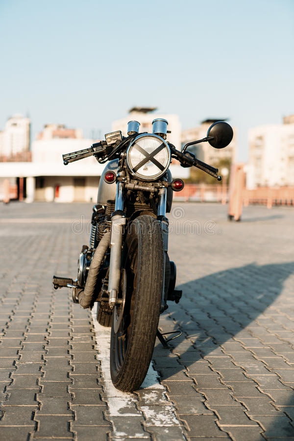 Silver vintage custom motorcycle caferacer. Front view of silver vintage custom motorcycle motorbike cafe racer on empty rooftop parking lot surrounded by urban stock photography